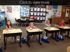 Four students color at their desks with book bins at their side