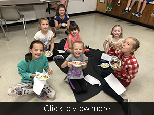 Students sit on a blanket and eat ice cream together
