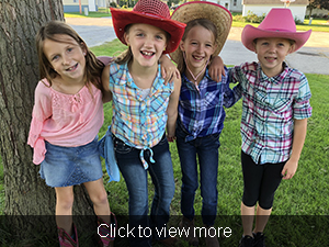 Four students in cowboy attire pose near a tree