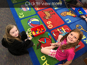 Click to view more. Two smiling female students play with blocks.