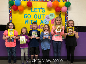 Click to view more. Six students pose with books in front of a sign reading Let's Go Out With A Bang.