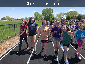 Click to view more. Female students walk around the track together.