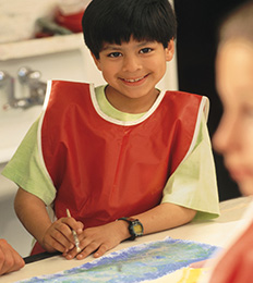 Male student wearing a smock participates in a painting activity