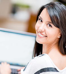 Smiling woman using a computer looks over her shoulder