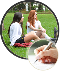 two students sitting in grass and hand with pen