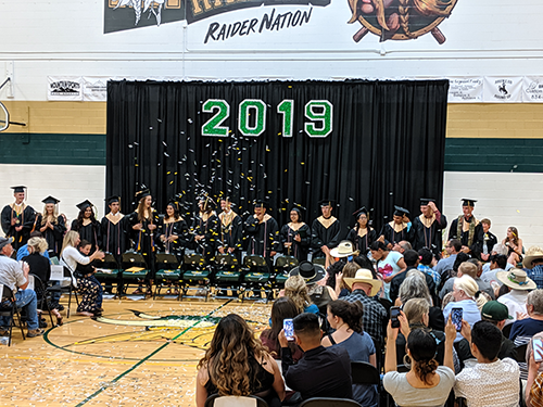 Class of 2019 standing on stage as the crowd cheers them on