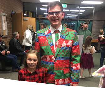 Teacher in Christmas suit with student