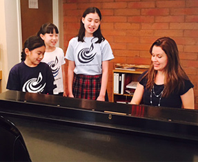 Three students sing as a woman plays piano