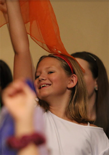 girl in a choir holding a scarf