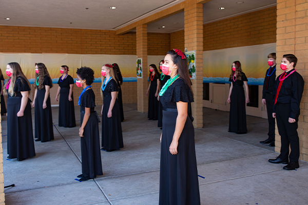 Choir members performing outside in masks and wearing leis