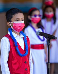 Young boy in red vest and blue lei singing at microphone