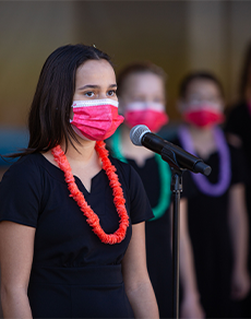 Teenage girl in black dress with red lei singing into microphone
