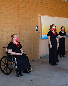 Teenage girl in wheelchair wearing a black dress with red lei