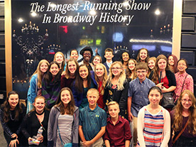 Chandler choir members pose in front of a sign reading The Longest-Running Show in Broadway History