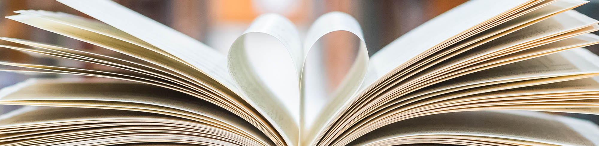 An open book with pages folded in a heart shape