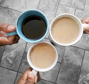 Adults holding three full cups of coffee