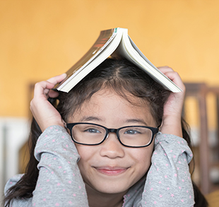 Smiling young girl with folding book on head