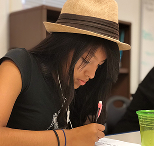 High school girl with hat focusing on writing assignment