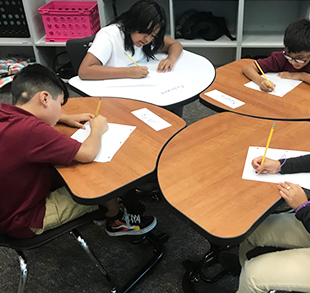 Students working at their desks on a writing assignment