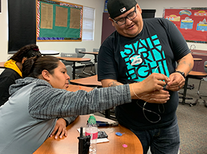 One person helping another in a classroom