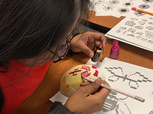 Student using paint in a classroom activity