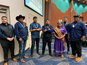Female student in formal cultural attire posing with six men