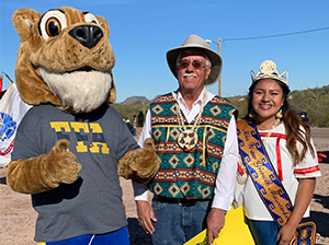 Female student poses with an adult and a mascot wearing an FFA t-shirt