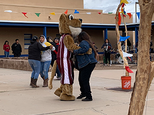 Person dancing with a mascot outside