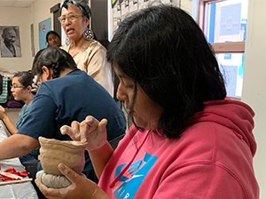 Female student working on a pottery activity
