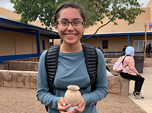 Smiling student holding up a ceramic pot