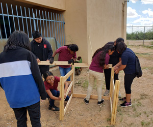 Group of students building a wooden structure