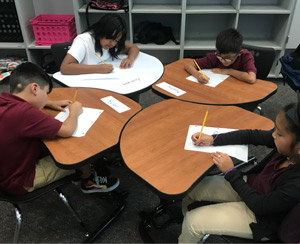 Four students sitting at their desks
