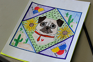 Ms. B's paper quilt square has a dog and some cactus with some flowers