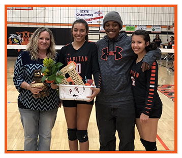 Teacher and students receiving awards during volleyball game