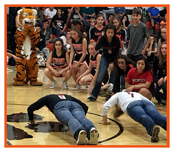 Students cheering on two students in a fun push-ups competition during a basketball game