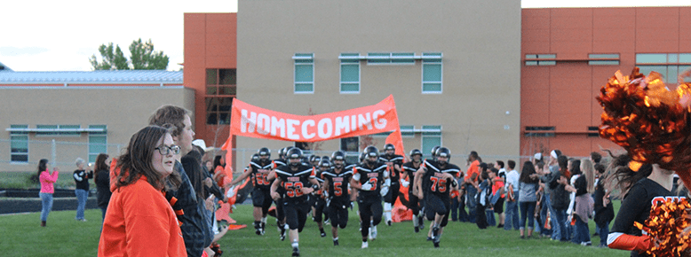 Football team running under a homecoming sign