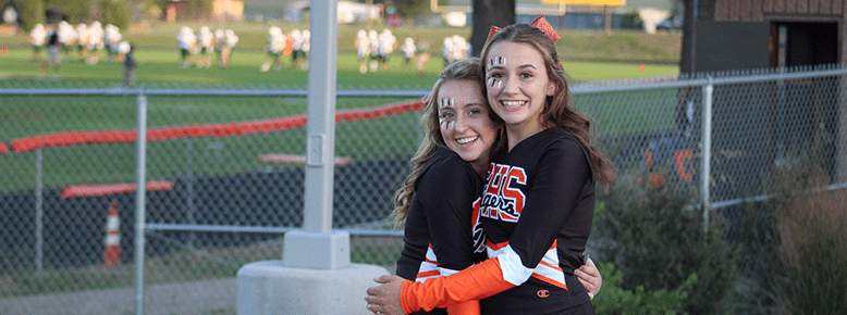 Two cheerleaders hugging near a football field