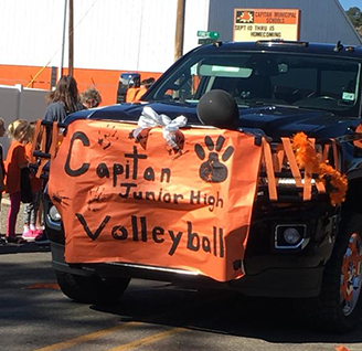 Black truck decorated with orange banner for Capitan Junior High Volleyball
