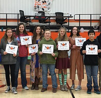 Group of happy middle schoolers holding up certificates in the gym