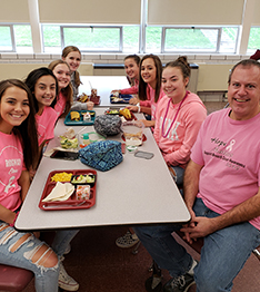 Group of happy students in pink with teacher in cafeteria
