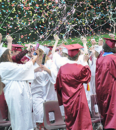 Students at graduation celebrating with confetti