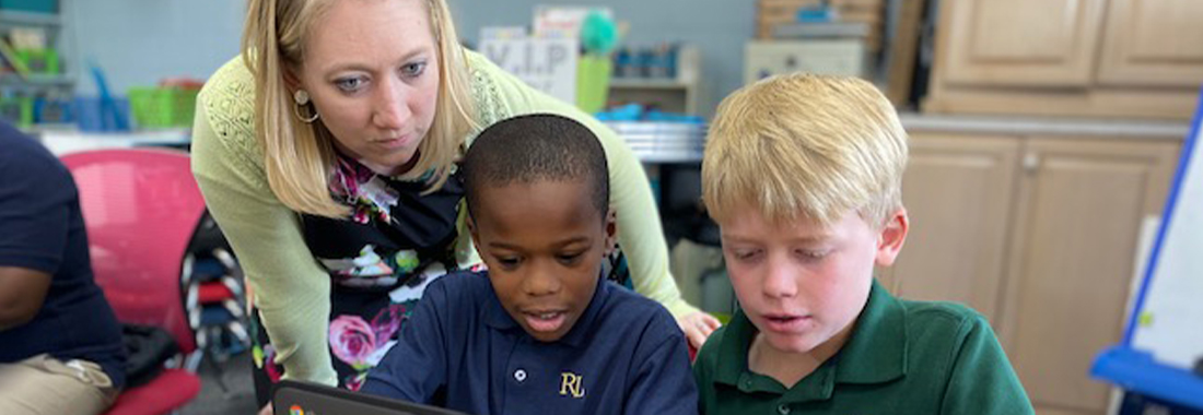 Teacher helping two students with chromebook