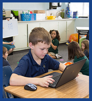 2nd grader working on a laptop in the classroom