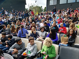 Students sit with their lunches in the theatre