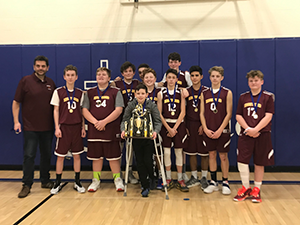 The eighth grade basketball team and their coach posing with their trophy