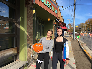 Two female students stand on a sidewalk holding a pumpkin