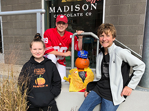 Two male students and one female student stand outside of Madison Chocolate Co with a pumpkin