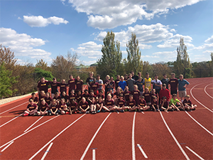 Track and field athletes and coaches pose together outside on the track