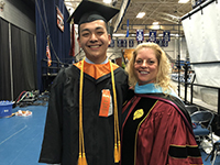 Graduate and teacher stand smiling next to each other