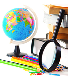 Magnifying glass, globe, colored pencils, paperclips and stacked books